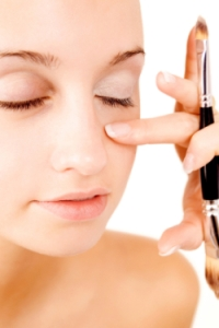 Applying concealer under eyes.
